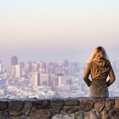 Frau sitzend auf Skyline schauend